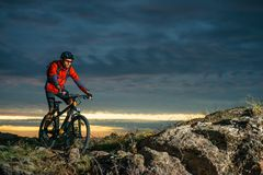 Cyclist in Red Riding the Bike on Autumn Rocky Trail at Sunset. Extreme Sport and Enduro Biking Concept. Cyclist in Red Riding the Bike on the Autumn Rocky Stock Photography