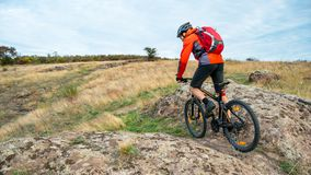 Cyclist in Red Riding the Mountain Bike on Autumn Rocky Trail. Extreme Sport and Enduro Biking Concept. Royalty Free Stock Photos