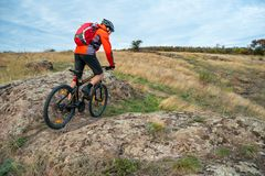 Cyclist in Red Riding the Mountain Bike on Autumn Rocky Trail. Extreme Sport and Enduro Biking Concept. Royalty Free Stock Photography