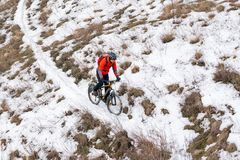 Cyclist in Red Riding Mountain Bike on the Snowy Trail. Extreme Winter Sport and Enduro Biking Concept. Royalty Free Stock Photography