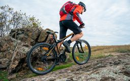 Cyclist in Red Riding the Mountain Bike up Autumn Rocky Trail. Extreme Sport and Enduro Biking Concept. Royalty Free Stock Image