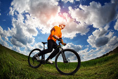 Cyclist in red sport equipment and helmet Stock Photos