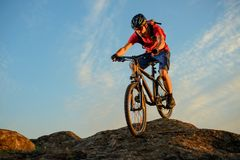Cyclist in Red Riding the Bike Down the Rock on the Blue Sky Background. Extreme Sport and Enduro Biking Concept. Stock Photos