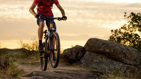 Cyclist in Red Riding the Bike on the Rocky Trail at Sunset. Extreme Sport and Enduro Biking Concept. Royalty Free Stock Photography