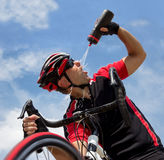 Cyclist refreshes from a bottle Royalty Free Stock Photo