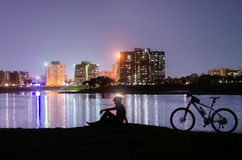 Cyclist relaxing infront of night cityscape. Cyclist traveling out of the city,close to the nature,sitting beside lake with his cycle,silhouette view Royalty Free Stock Image
