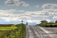 Cyclist on a remote road Stock Photo