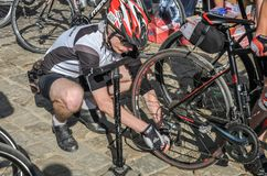 LVIV, UKRAINE - MAY 2018: The cyclist repairs his bicycle by pumping a punctured wheel. The cyclist repairs his bicycle by pumping a punctured wheel royalty free stock images