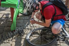 LVIV, UKRAINE - MAY 2018: The cyclist repairs his bicycle by pumping a punctured wheel. The cyclist repairs his bicycle by pumping a punctured wheel royalty free stock photos