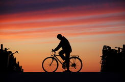 Cyclist At Rest. A cyclist taking a break against a beautiful sunset at the beach in Scheveningen, Holland royalty free stock images