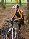 Cyclist resting on a bench in nature Royalty Free Stock Photos