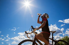 Cyclist resting and drinking isotonic drink. Royalty Free Stock Photo
