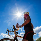 Cyclist resting and drinking isotonic drink. Road cyclist resting and drinking isotonic drink. Backlight, sunny summer day Royalty Free Stock Images