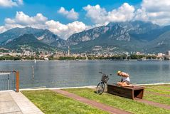 Cyclist resting on the Lakefront of Malgrate located on the shore of Como Lake in province of Lecco. Cyclist resting on the Lakefront of Malgrate located on the Stock Image