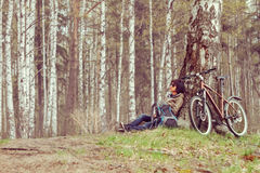Cyclist rests in a forest Royalty Free Stock Images