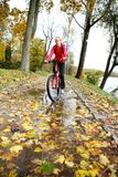 Cyclist ride through a puddle in the autumn park Stock Photo