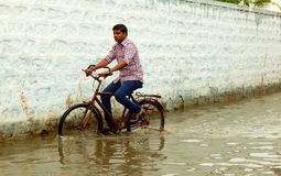 Cyclist ride in rain water flooded road Stock Photo