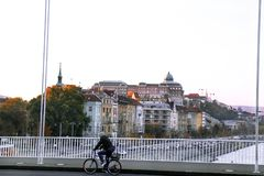 Cyclist rides a bicycle across the bridge, and in the background Royalty Free Stock Photo