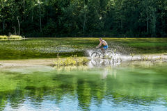 Cyclist rides a bicycle across the river at the ford Royalty Free Stock Photography