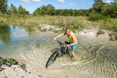 Cyclist rides a bicycle across the river at the ford Stock Photo