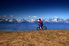 Cyclist rides a mountain bike before snow-covered peaks Stock Images