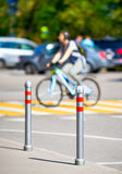 Cyclist rides on a pedestrian crossing. In the foreground metal bollards Stock Photography