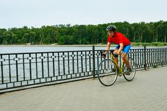 A cyclist rides on a road bicycle along lake. Royalty Free Stock Photo