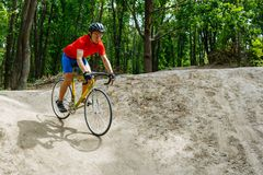 A cyclist rides on a road bicycle, coming down hill. Royalty Free Stock Images