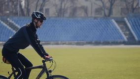 Cyclist rides on a stadium stock footage