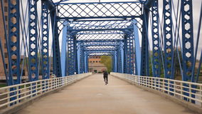 Cyclist Riding Across Blue Bridge Grand Rapids Michigan Bicycle Rider. Man rides across the bridge from downtown to the university stock footage