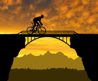 Cyclist riding across the bridge Royalty Free Stock Photo