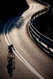 Cyclist riding along a mountain road Royalty Free Stock Image