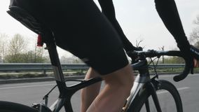 Cyclist riding a bicycle and changing gears. Close up follow shot. Cyclist pedaling on bicycle in motion. Slow motion.  stock video footage