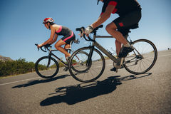 Cyclist riding bicycles down hill on country road Royalty Free Stock Photography