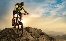 Cyclist Riding the Bike on Autumn Rocky Trail at Sunset. Extreme Sport and Enduro Biking Concept. Cyclist Riding the Bike on the Autumn Rocky Trail at Sunset stock photo