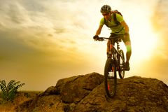 Cyclist Riding the Bike on Autumn Rocky Trail at Sunset. Extreme Sport and Enduro Biking Concept. Stock Images