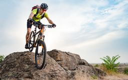 Cyclist Riding the Bike on Autumn Rocky Trail at Sunset. Extreme Sport and Enduro Biking Concept. royalty free stock images