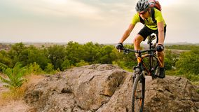 Cyclist Riding the Bike on Autumn Rocky Trail at Sunset. Extreme Sport and Enduro Biking Concept. stock photos