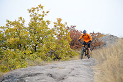 Cyclist Riding Bike on the Beautiful Autumn Mountain Trail Royalty Free Stock Photography