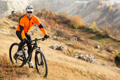 Cyclist Riding the Bike on the Beautiful Spring Mountain Trail. Cyclist in the helmet and the gkasses. Travel in the countryside. Beautiful landscape with hill royalty free stock images