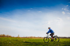 Cyclist Riding the Bike. On the Beautiful Summer Meadow trail royalty free stock photo