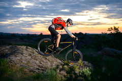 Cyclist Riding the Bike Down Hill on Mountain Rocky Trail at Sunset Royalty Free Stock Photos