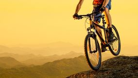 Cyclist Riding the Bike Down the Rock at Sunset. Extreme Sport and Enduro Biking Concept. Royalty Free Stock Images