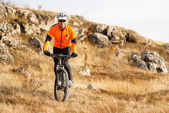 Cyclist Riding the Bike Down Rocky Hill. Extreme Sport Concept. Space for Text. Royalty Free Stock Images