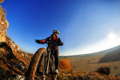 Cyclist Riding the Bike Down Rocky Hill at Sunset. Close up Extreme Sport Concept. Space for Text. Royalty Free Stock Images