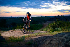 Cyclist Riding the Bike on Mountain Rocky Trail at Sunset Stock Photo
