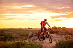Cyclist Riding the Bike on Mountain Rocky Trail at Sunset Royalty Free Stock Image