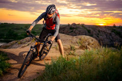 Cyclist Riding the Bike on Mountain Rocky Trail at Sunset Stock Images