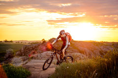 Cyclist Riding the Bike on the Mountain Rocky Trail at Sunset Royalty Free Stock Photography