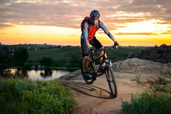 Cyclist Riding the Bike on the Mountain Rocky Trail at Sunset Stock Photography